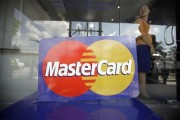 An employee stands behind a MasterCard logo during the launch of the international credit card issuer's first ATM transaction in Myanmar, in Yangon November 15, 2012.