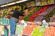 Mexican immigrant working arranging fruit in a convenience store