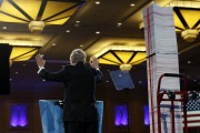 Senate Minority Leader Mitch McConnell acknowledges supporters as he stands next to a stack representing