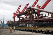 Workers walk near a cargo ship at the Beira port in Mozambique, February 15, 2013. Mozambique has named miner Rio Tinto as one of six preferred bidders for a new $3 billion railway and port developmen