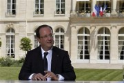 French President Francois Hollande speaks with journalists after a television interview in the garden of the Elysee Palace, following the traditional Bastille day military parade in Paris July 14, 201