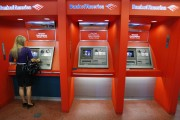 A woman withdraws money from a Bank of America automatic teller machine in New York's financial district September 16, 2008. Bank of America Corp's $50 billion acquisition of Merrill Lynch & Co would