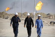 Iraqi workers walk in West Qurna oilfield in Iraq's southern province of Basra November 28, 2010.