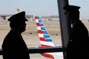 Pilots talk as they look at the tail of an American Airlines aircraft following the announcement of the planned merger of American Airlines and US Airways, at Dallas-Ft Worth International Airport