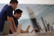 Apple Store employees look at a display of MacBook laptops during a press preview of the new flagship Apple Store.