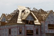 A builder works on the the roof of a new home under construction