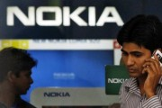 A customer speaks on his mobile phone as he comes out of a Nokia showroom in New Delhi March 28, 2013.